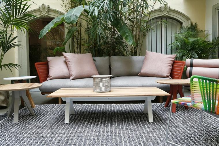 Alberi da giardino sempreverdi, arredamento con un divano in legno e tavolino rettangolare