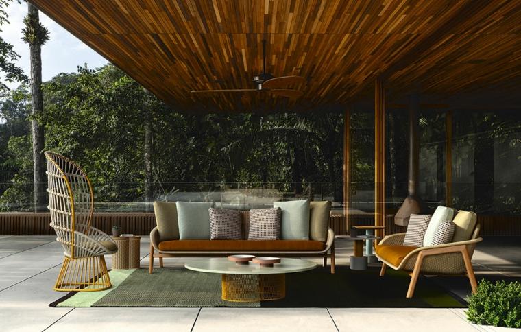 Idee giardino piccoli, arredamento con mobili di legno e rattan, tavolino rotondo su un tappeto verde