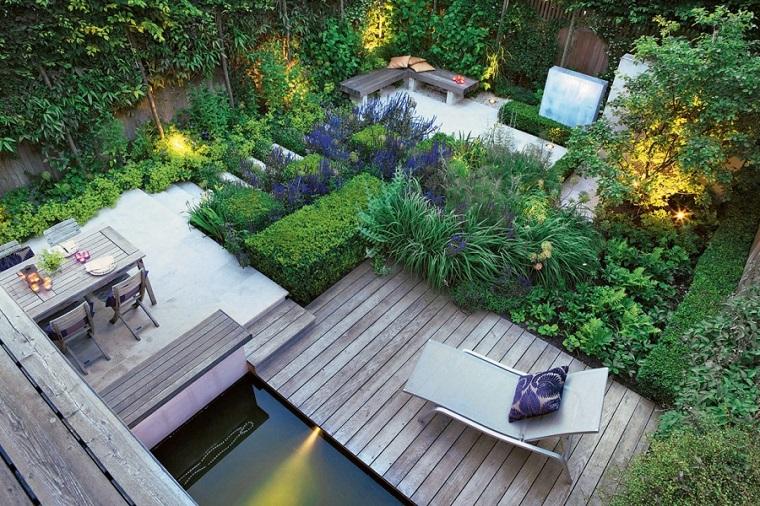 Un giardino con dislivelli e tante piante sempreverdi e rampicanti, arredamento con mobili in legno e uno sdraio