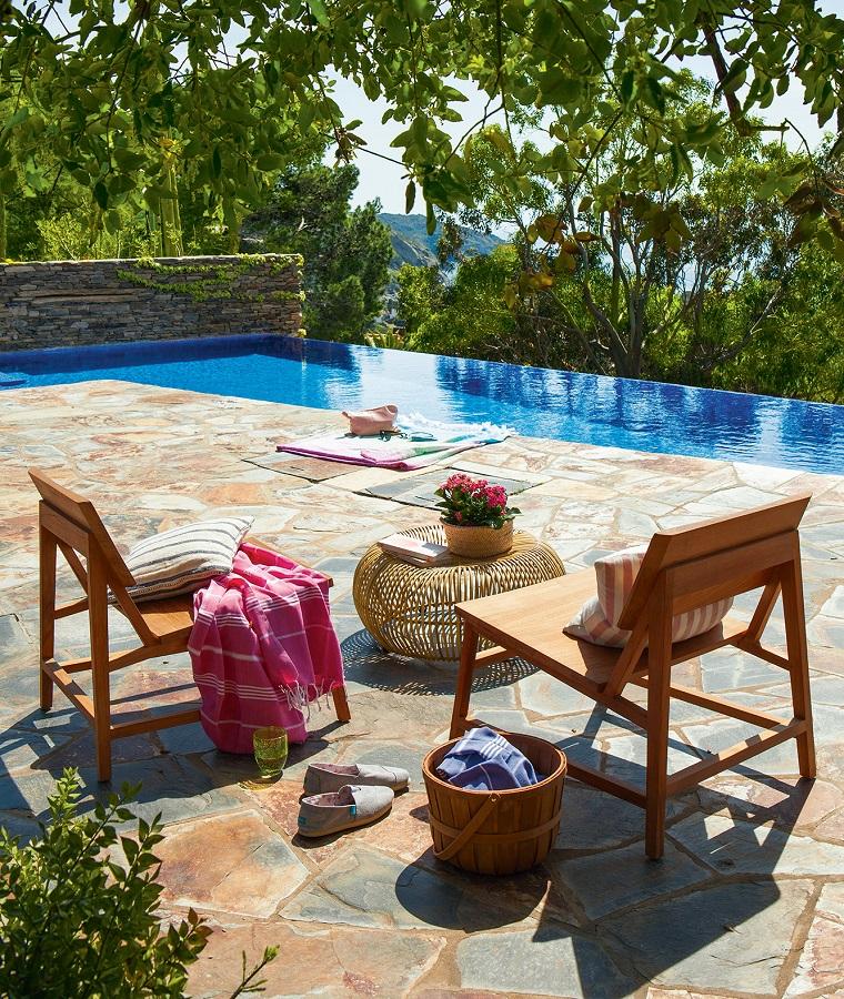 Piscina e mobili in legno, alberi da giardino sempreverdi e una pavimentazione effetto pietra