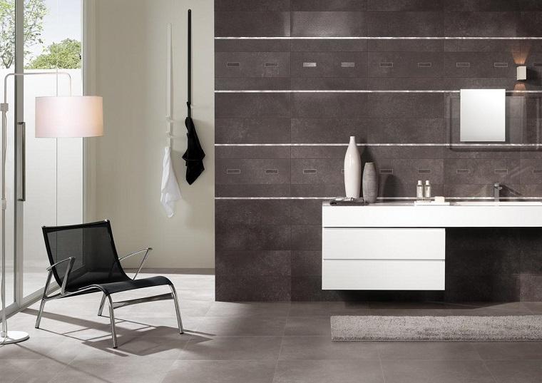Arredare la sala da bagno con un mobile bianco con lavabo da incasso e una poltrona di metallo nera