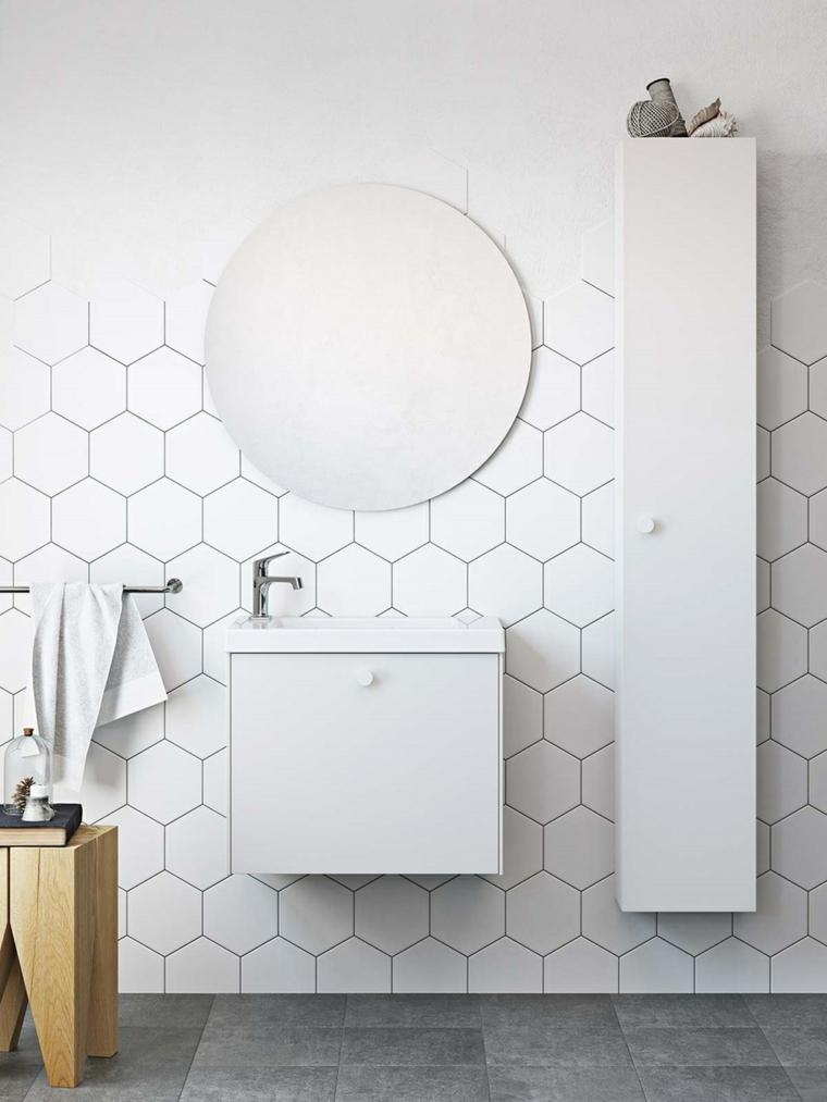 Mobile lavabo piccolo di colore bianco e armadietto lungo, piastrelle bianche e specchio rotondo