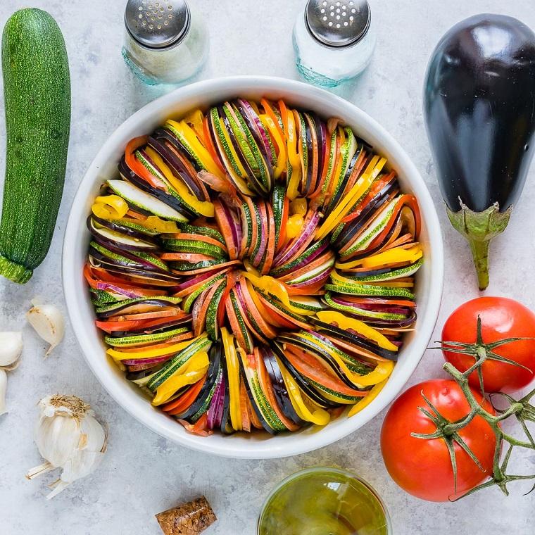 Ricette secondi piatti, idea per una ratatouille di verdure tagliate a rondelle in pirofila rotonda