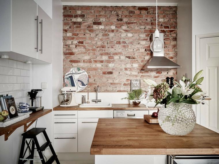 cucina con mobili bianchi e top in legno, cappa in acciaio inox e tavolo quadrato e muri in pietra per interni