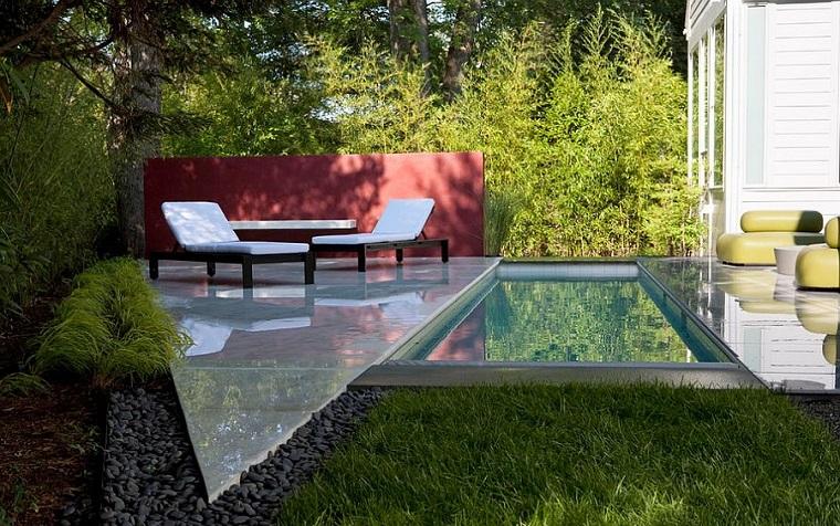 Alberi da giardino sempreverdi, piscina rettangolare e due sdrai di legno con cuscineria di colore bianco