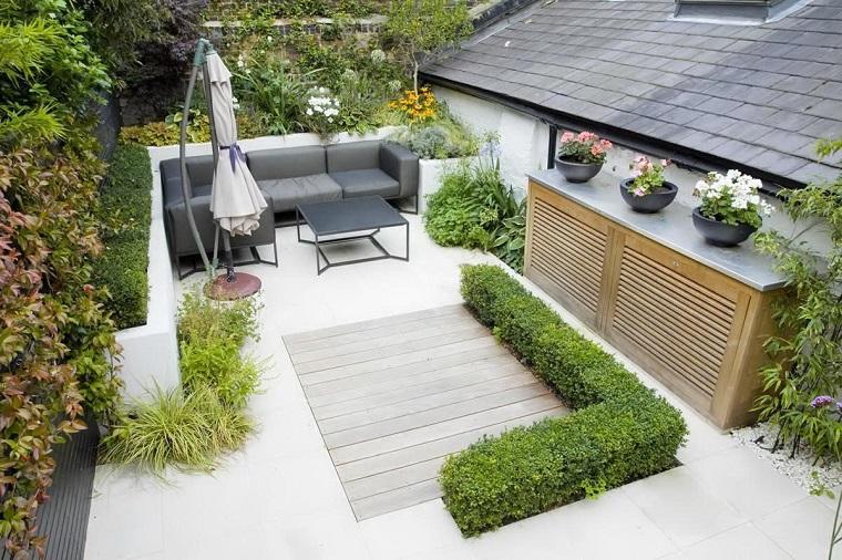 Alberi da giardino sempreverdi, arredamento con un divano in pelle e ombrellone