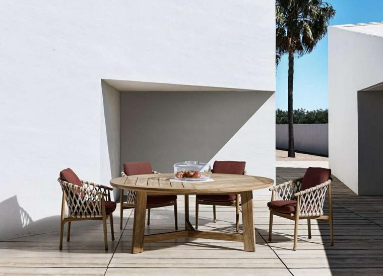 Mobili da esterno in legno con cuscini rossi, giardino minimalista con pareti della casa bianche