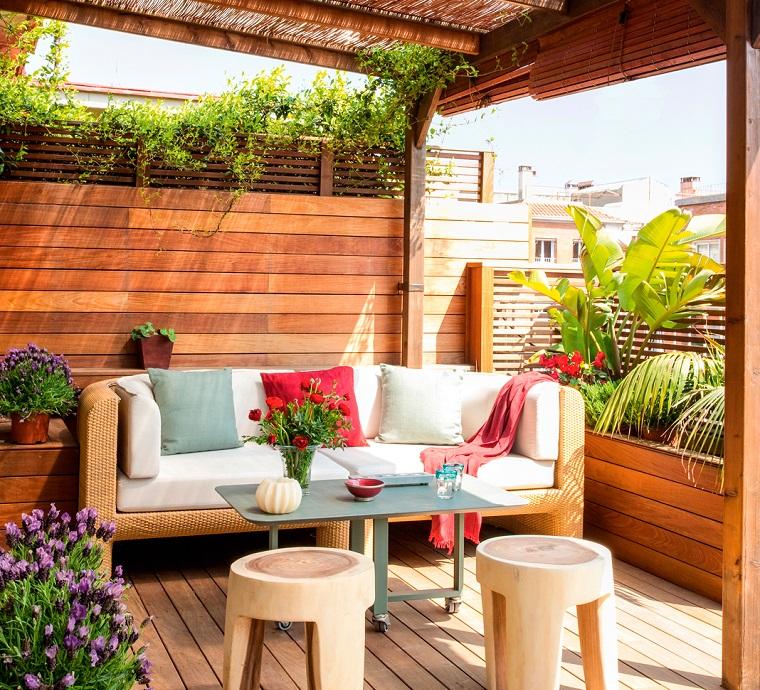Idee giardino piccolo con un divano in rattan e cuscini colorati, parete con travi in legno e pergola