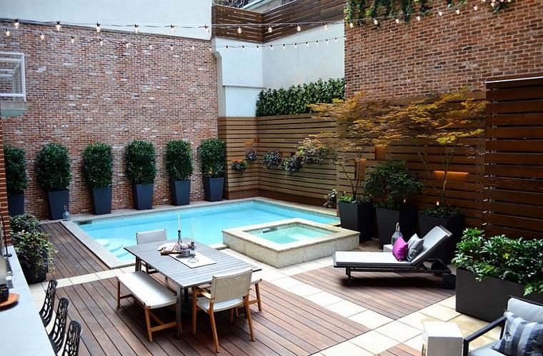 Giardino con recinzione in legno e una piccola piscina, arredamento con un tavolo da esterno e sedie