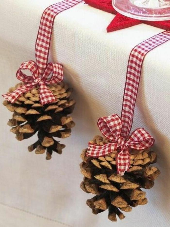 Decorare il tavolo natalizio con delle pigne pendenti su un filo di colore rosso e bianco
