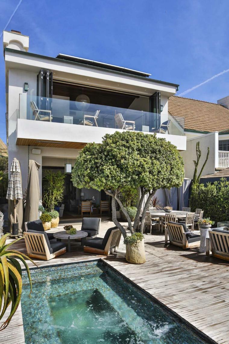 Un giardino lungo e stretto con piscina e due zone giorno arredate con mobili in legno