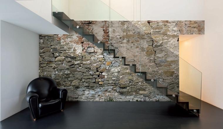 pavimento nero opaco e poltrona in pelle in stile vintage, scala moderna e parete interna in pietra