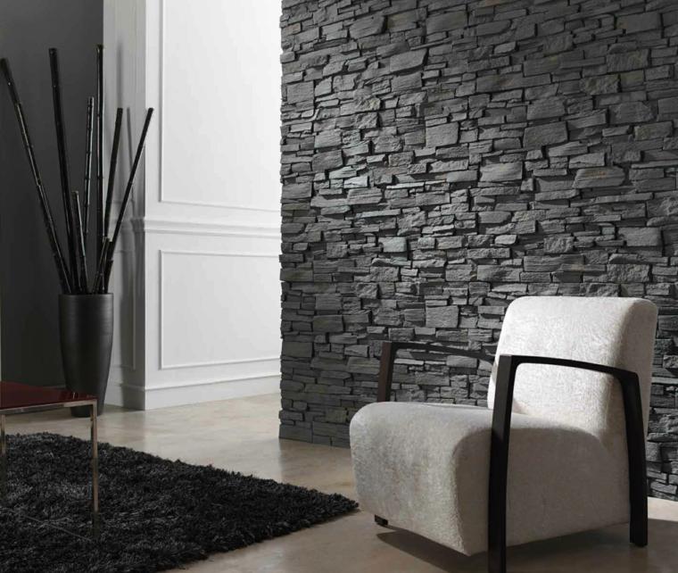 vaso grigio con rami neri, tappeto nero, poltrona bianca squadrata con braccioli neri e pareti in pietra