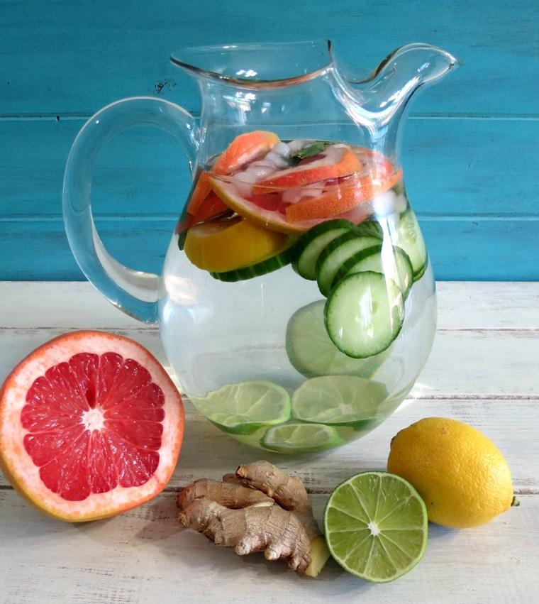 Caraffa di vetro con acqua e frutta tagliata a pezzettini, agrumi e radice di zenzero su un tavolo di legno