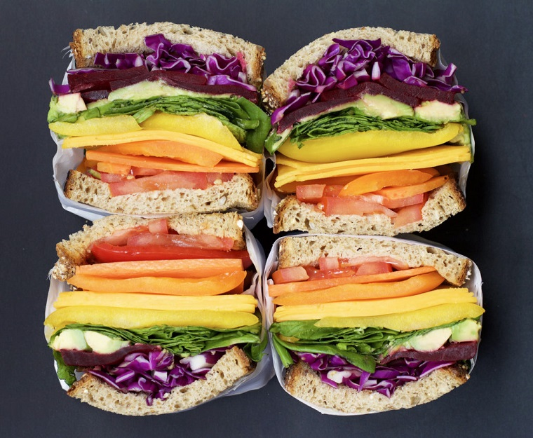 Panini con pane integrale e verdure tagliate a julienne, quattro sandwich incartati