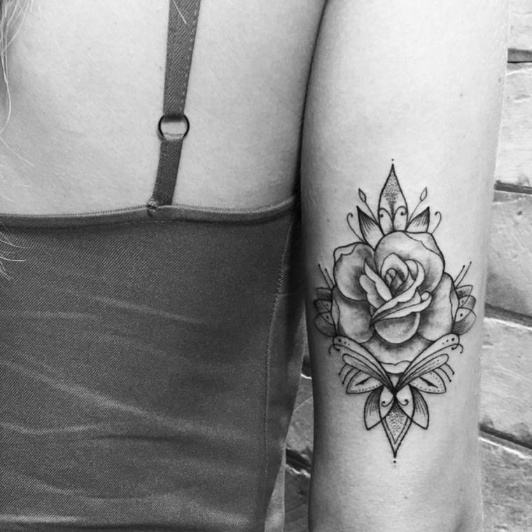 bellissima idea per rose tatuate sul braccio in bianco e nero con delle foglie stilizzate