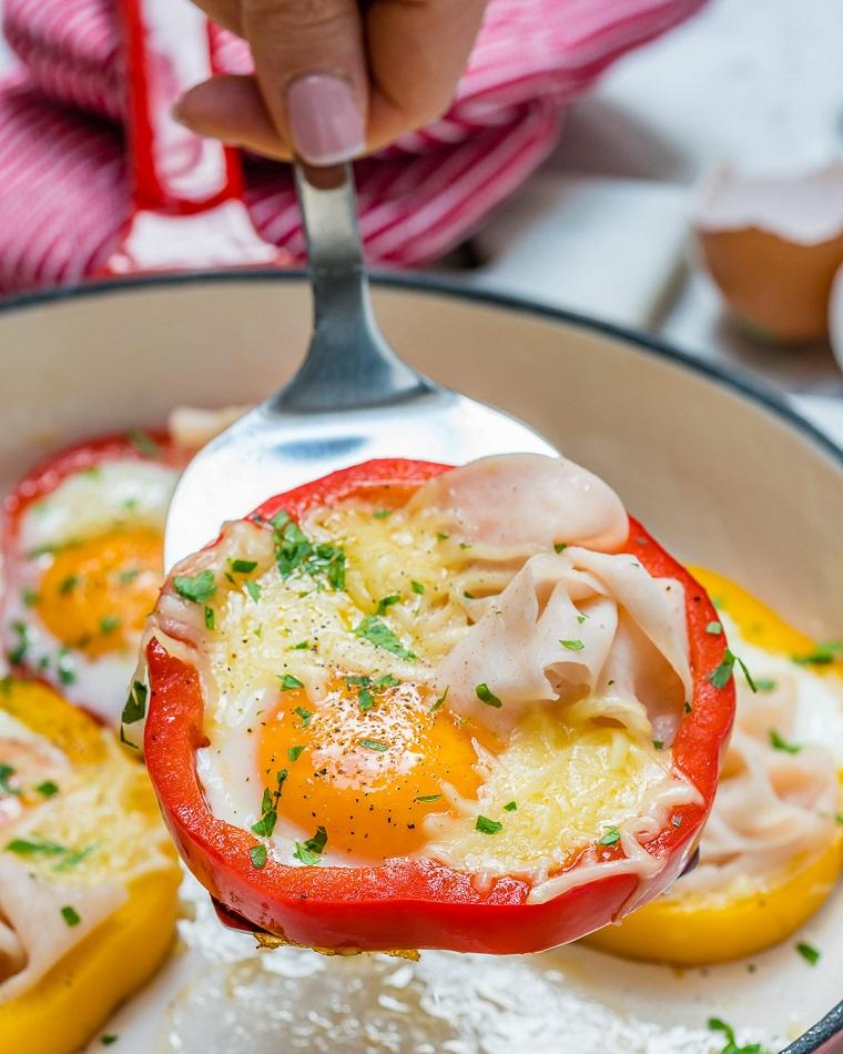Secondi piatti semplici e gustosi con uova e fette di prosciutto, peperone rosso tagliato ad anello come base