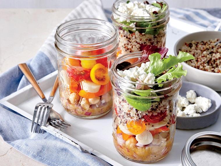 Barattoli di vetro con pomodorini e mozzarelline, ceci e quinoa per un pranzo leggero