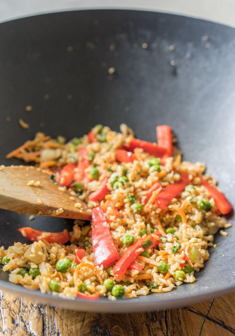 Ricette veloci estive per cena, risotto preparato in una padella wok con verdure tagliate a julienne