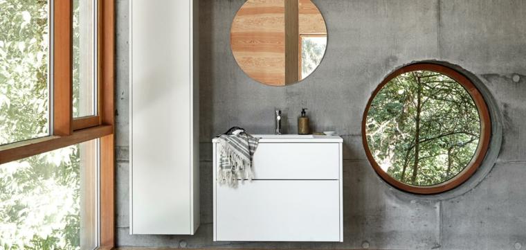 Bagno arredato con un armadietto e mobile lavabo sospeso, parete colore grigio con specchio rotondo e finestra