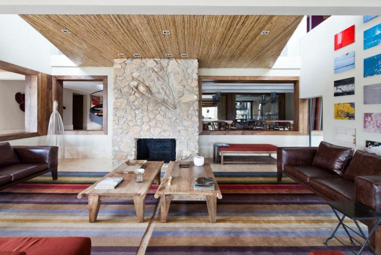 salotto dallo stile rustico moderno con divano in pelle marrone, tappeti a righe colorate e camino in pietra