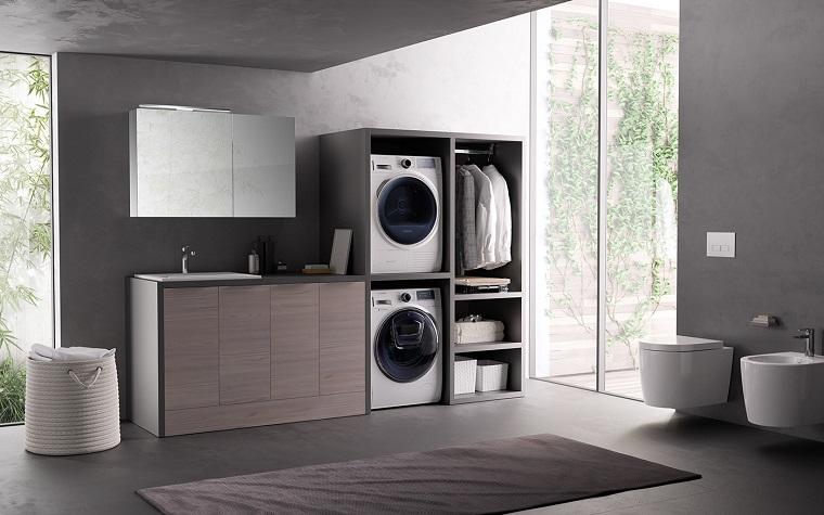 Arredare il bagno grande con lavanderia e mobili di legno, pareti e pavimento di colore grigio