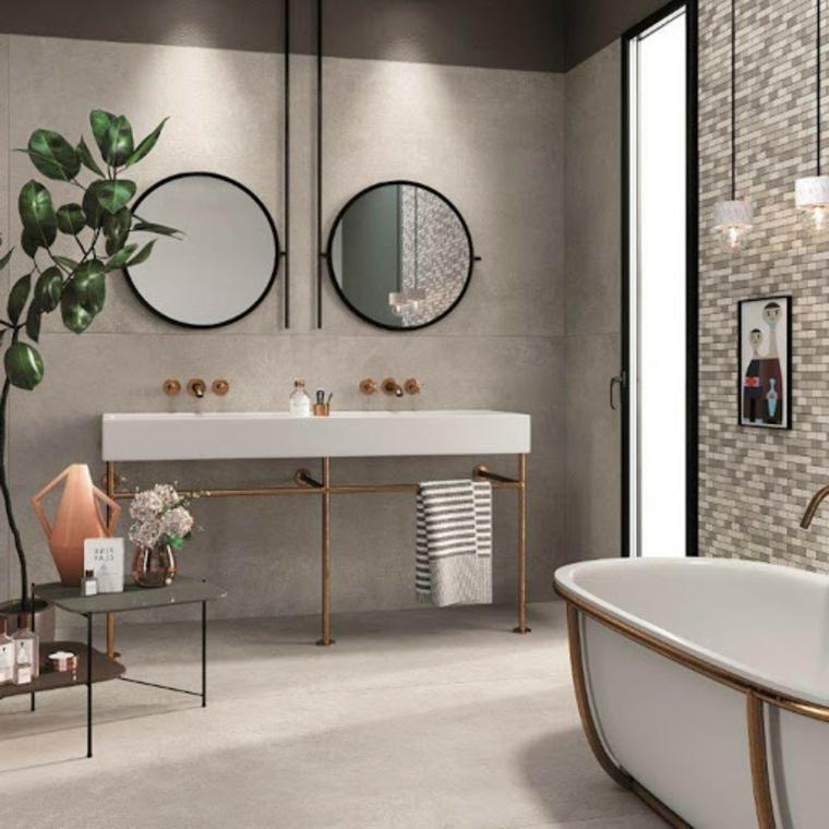 Sala da bagno con vasca freestanding, mobile con due lavandini e specchi rotondi sulla parete