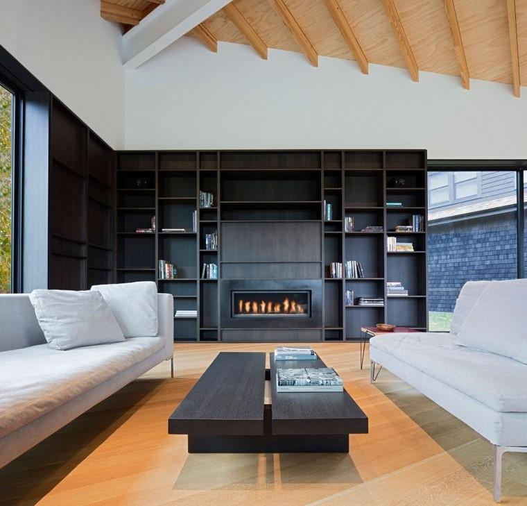 Come arredare un soggiorno con parete a nicchie di legno e due divani di colore bianco