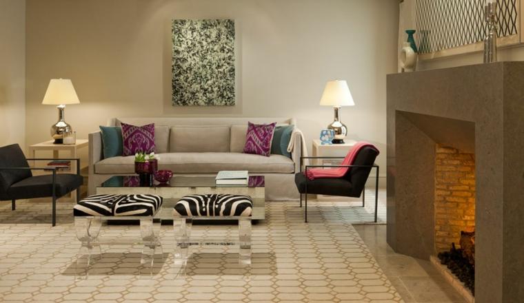 salotto luminoso arredato con un divano lineare beige e due poltrone nere, camino e muri color tortora