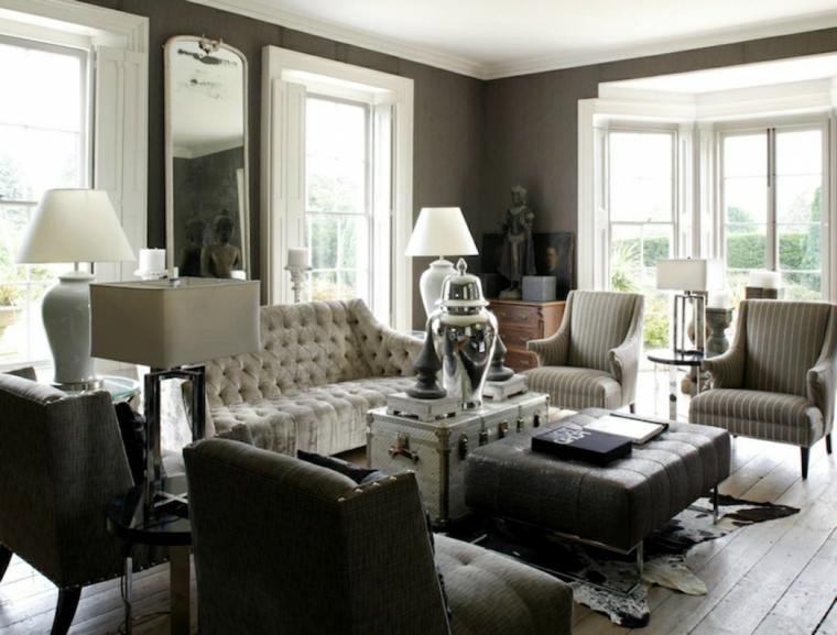 zona living arredata con poltrone e divani eleganti , pavimento in parquet, specchio rettangolare e pareti tortora
