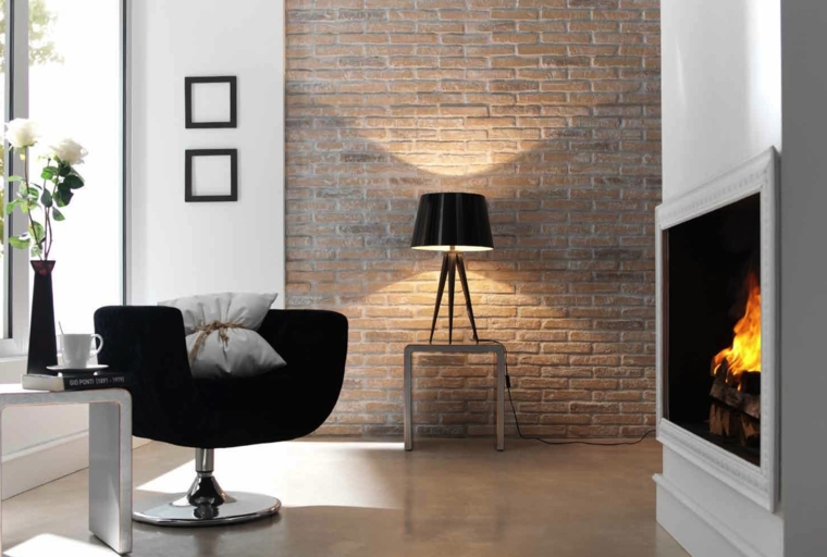 camino in stile moderno, poltrona nera con piantana in acciaio, lampada da tavolo e pareti rivestite in pietra