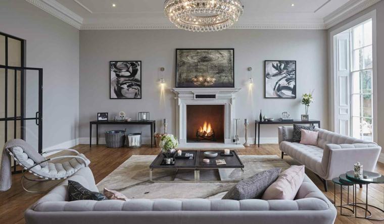 salotto con camino a legna decorazione pareti con quadri set di divani colore tortora