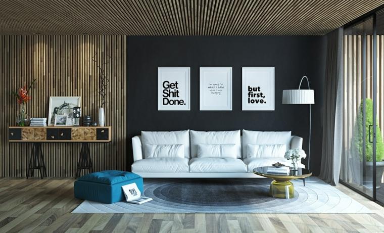 Zona giorno parete di colore nero e tre quadri moderni, divano di pelle bianco con tavolino di design
