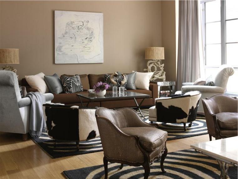 soggiorno arredato con diverse poltrone eleganti, un divano con cuscini, tappeti bianchi e neri, esempio abbinamenti color tortora