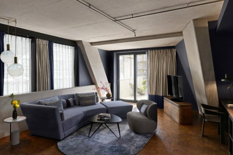Zona giorno con un divano di colore blu con tavolino di legno nero