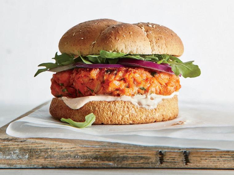 Panino con hamburger di pesce e verdure, pezzettini di cipolla rossa e rucola
