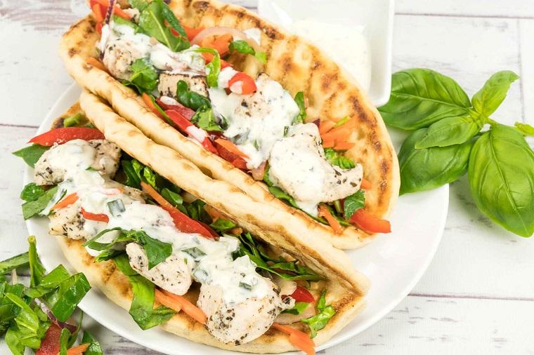 Due panini con pane e fette di pomodoro, pollo e salsa bianca, condimento con foglie di basilico