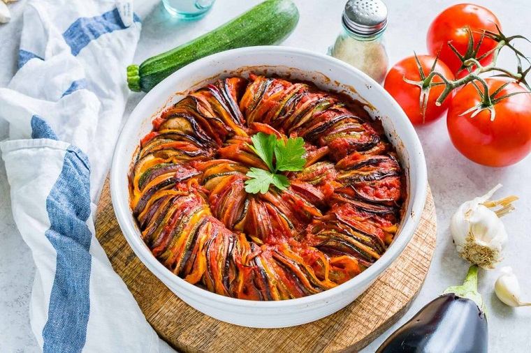 Ratatouille con verdure in una teglia rotonda, piatti estivi veloci per una cena vegetariana
