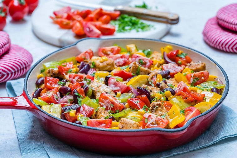 Ricette veloci cena con verdure e pollo in un tegame di colore rosso, condito con prezzemolo tritato