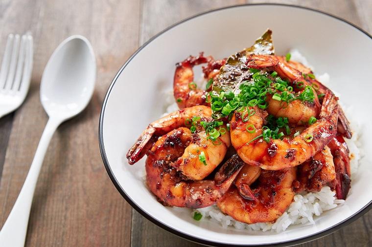 Ciotola con del risotto bianco e scampi alla grigia in marinata, servito su un tavolo di legno