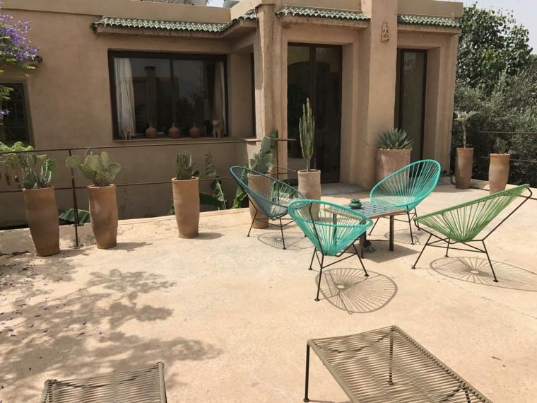 Arredamento di un giardino piccolo con sedie di metallo colorate e decorato piante da giardino grasse