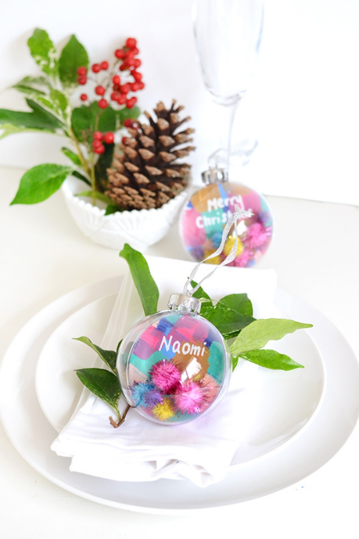 Tavole natalizie, palline trasparenti, segnaposti con foglie verdi
