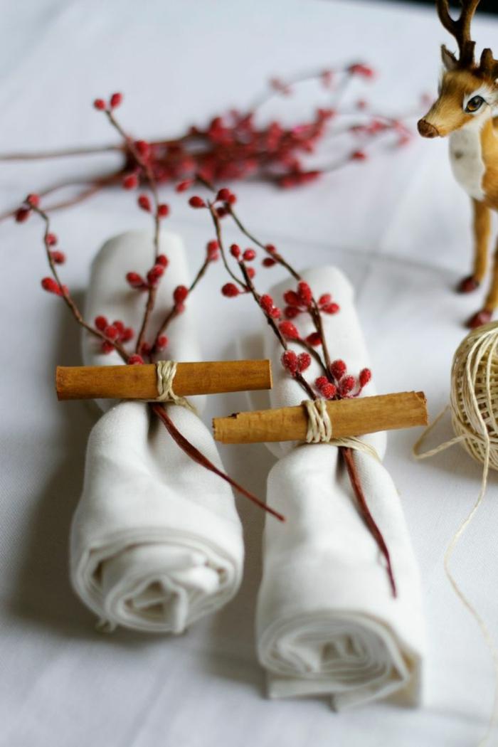 Tovaglioli piegati, segnaposti con bacche rosse, tavolo apparecchiato