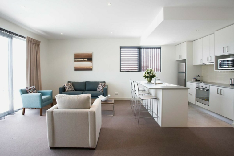 come arredare cucina soggiorno ambiente unico con mobili della cucina bianchi, isola e sgabelli, poltrone e divano grigio