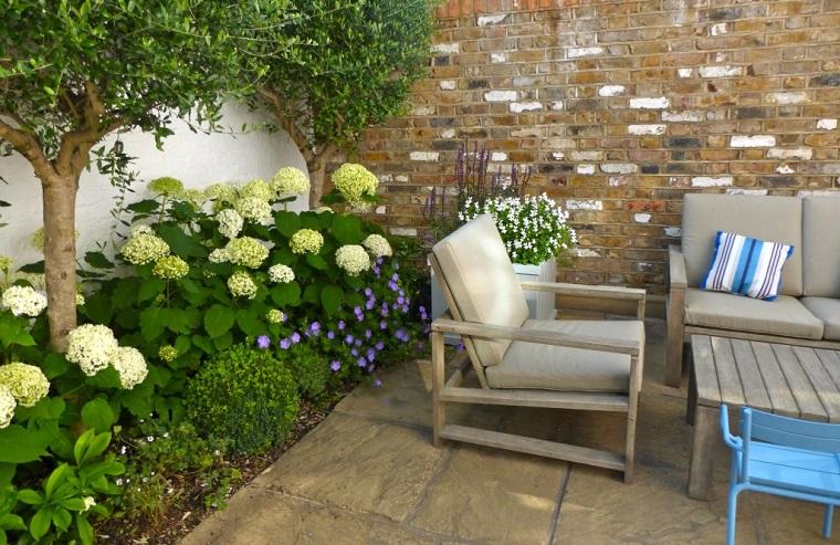 Tanti fiori fioriti e alberi verdi, arredamento con un set da esterno in legno e cuscineria grigia