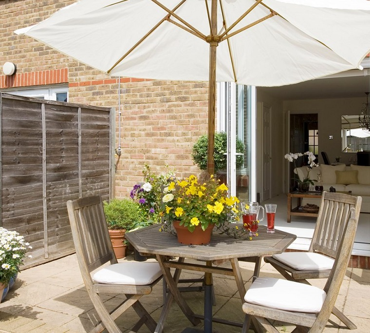 Piante da giardino, arredamento con mobili di legno e un ombrellone di colore bianco