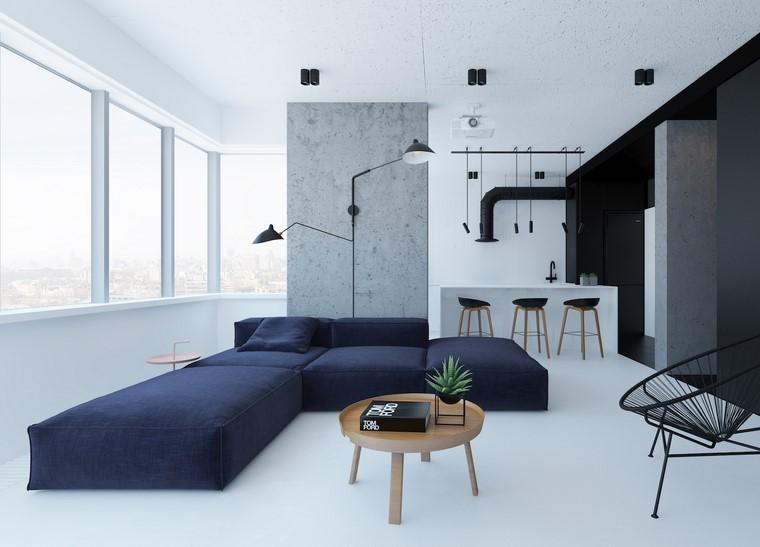 Open space cucina soggiorno e un divano di colore blu con penisola, tavolino rotondo in legno abbinato