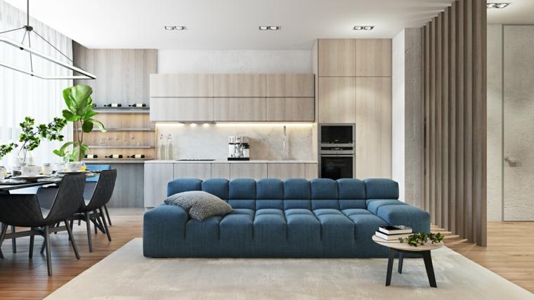 Open space cucina soggiorno, arredamento con un divano di colore blu e una parete divisoria con travi di legno