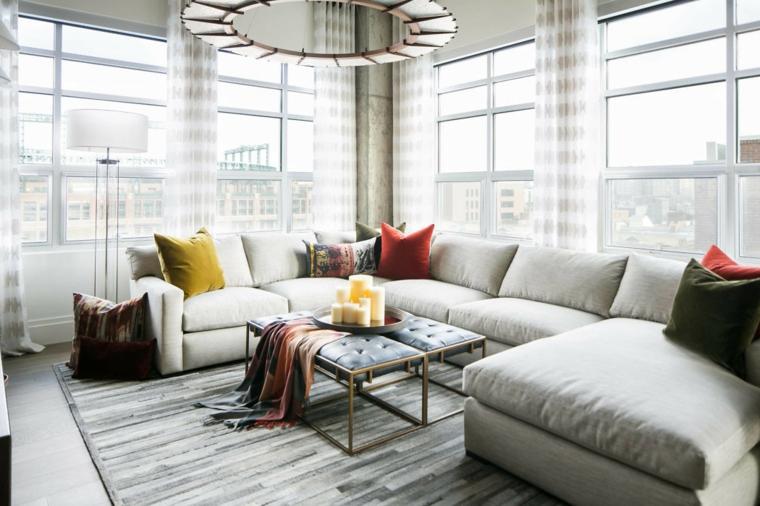 Come arredare un soggiorno con un divano angolare di colore grigio, decorazioni con tante candele di cera