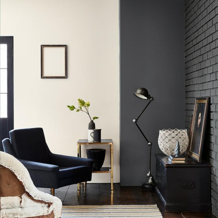 soggiorno color tortora parete con mattoni grigi pavimento piastrelle scure e tappeto